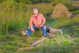 stock photo of haystacks  - Farmer with an axe sitting near haystack - JPG