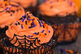 stock photo of sprinkling  - Halloween cupcakes with sprinkles closeup with shallow depth of field - JPG