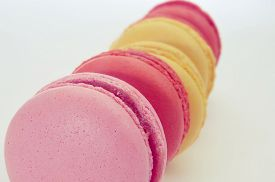 image of flavor  - closeup of some appetizing macarons of pastel colors and different flavors on a white background - JPG