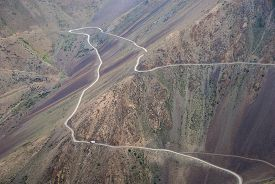 pic of long winding road  - Big track on the long winding high mountain road - JPG
