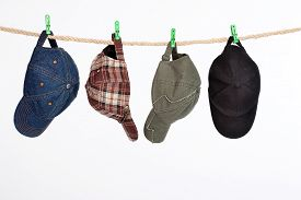 pic of clotheslines  - Different hats and caps hanging on a clothesline - JPG