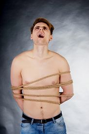 image of torture  - Tortured shirtless man tied with a rope - JPG