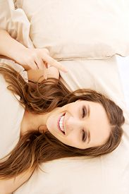 image of middle finger  - Young happy woman showing middle finger in bedroom - JPG