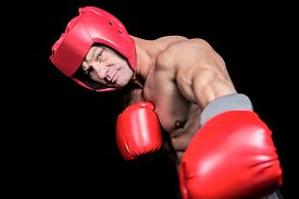 picture of headgear  - Portrait of boxer with gloves and headgear punching against black background - JPG