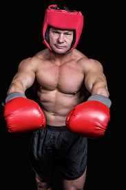 picture of headgear  - Portrait of boxer with red gloves and headgear against black background - JPG