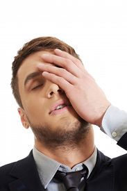 picture of forehead  - Handsome worried businessman touching his forehead - JPG
