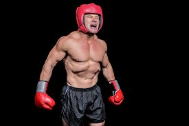 foto of headgear  - Angry boxer with gloves and headgear against black background - JPG