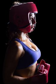 stock photo of headgear  - Side view of female boxer with headgear and gloves against black background - JPG