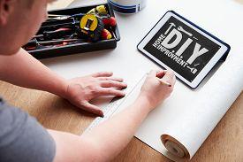 stock photo of tin man  - Man Plans Design Project Using Application On Digital Tablet - JPG