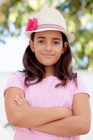 stock photo of ten years old  - Nice child girl ten year old with a hat on the street - JPG