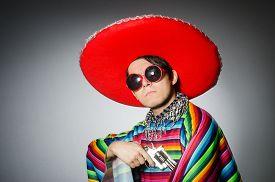 foto of handgun  - Man in vivid mexican poncho holding handgun against gray - JPG