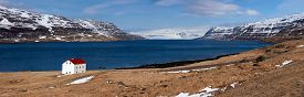 stock photo of iceland farm  - Quaint isolated farm house along the fjord westfjords surrounded by mountains covered in snow in Iceland - JPG