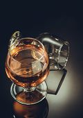 cognac glass on black glossy background poster