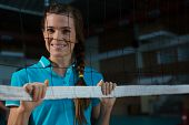 Portrait of happy female volleyball player standing behind net at court poster