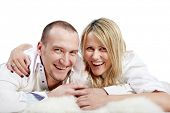 Man and woman in white shirts lie on the white carpet and laugh merrily, looking before itself.