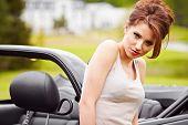 Sexy woman posing next to cabrio car