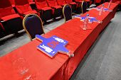 Long judge table with  red table-cloth on which cards lie stands in empty hall