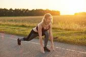 Attractive Female Wearing Sport Shoes And Clothes, Doing Sport Exercises On Road Against Sunset, Lik poster