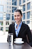 picture of drinking water  - businesswoman having break outdoor drinking coffee and water - JPG