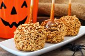 Halloween Caramel Apples With Nuts On A Plate With Jack O Lantern Candy Pail In Background poster