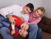young couple playing with their children at home, family concept