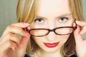 Young blond businesswoman looking over her black rim glasses