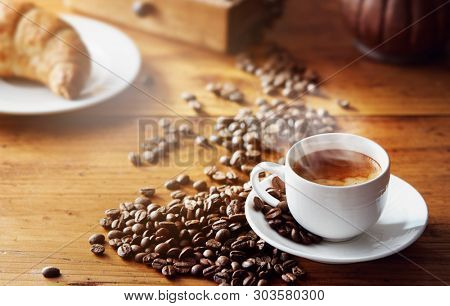 poster of A steaming cup of coffee with coffee beans and a croissant on vintage wooden table.
