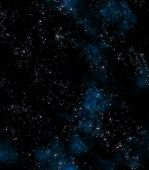 stock photo of starry sky  - lots of stars in outer space with blue nebula clouds - JPG