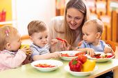 Kids Have A Lunch In Day Care Centre. Children Eating Healthy Food In Kindergarten. Nursery Teacher  poster