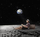 Young man sitting on the Moon and reading a book with Earth in the background