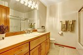 image of outdated  - Simple white bathroom with wood cabinets and white walls - JPG
