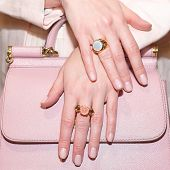 Woman Hands With Manicure And Luxury Jewelry Rings. Close Up Of Trendy Leather Pink Bag With Female  poster