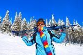 Joven esquiadora hombre sosteniendo el esquí; chaqueta azul; pantalón negro; orientación horizontal