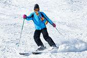 Joven esquiadora masculino en nieve en polvo; chaqueta azul; pantalón negro; orientación horizontal