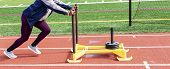 A High School Shot Put Girl Is Pushing A Yellow Sled With Seventy Five Pounds Of Weight On It Down A poster