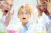 Three shocked scientists looking at the obtained substance expressing intense emotions