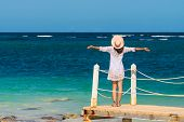 Beautiful Woman On Docks With Hands Outstretched. Vacations Lifestyle. Woman Relaxing On The Beach.  poster