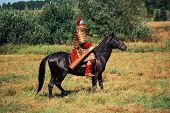 An Ancient Equestrian In Historical Costume Is Reconstructed. The Medieval Armored Knight Is On The  poster