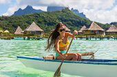 Outrigger Canoe - woman paddling in traditional French Polynesian Outrigger Canoe for recreation wat poster