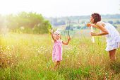 Mother And Little Girl Daughter Child Blowing Soap Bubbles Outdoor. Parent And Kid Having Fun On Mea poster