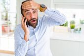 Handsome hispanic business man having a conversation talking on smartphone stressed with hand on hea poster