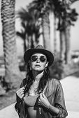 Pretty Brunette Girl In Hat And Sunglasses Walking Outdoor Near Sea. poster