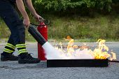 stock photo of fireman  - Instructor showing how to use a fire extinguisher on a training fire - JPG