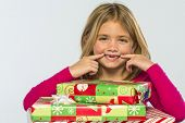 Young girl with missing teeth shows excitement with presents