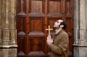 man monk praying to the front door of the church holding cross crucifix