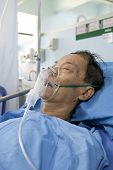 stock photo of oxygen mask  - old man wearing oxygen mask asleep on patient bed - JPG