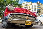 HAVANA-DECEMBER 14:Shiny red 1957 Buick waiting for tourists near a hotel December 14,2012 in Havana