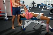 Trainer helping girl to train in the gym Bar Bench Press