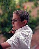 picture of fletching  - Close up of a young boy drawing back a bow and arrow