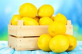 Ripe lemons in wooden box on table on bright background